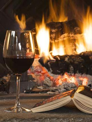 glass of wine and book by fireplace sky