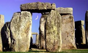 Stonehenge with a new moon seen through standing stones