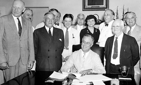 Franklin D. Roosevelt signs the Social Security Act of 1935