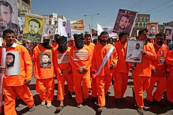 Yemeni protestors dressed in prison uniforms, hold posters of men detained in Guantanamo Bay prison during a demonstration in front of the U.S. embassy demanding their release, in Sanaa, Yemen, Tuesday, April 16, 2013.