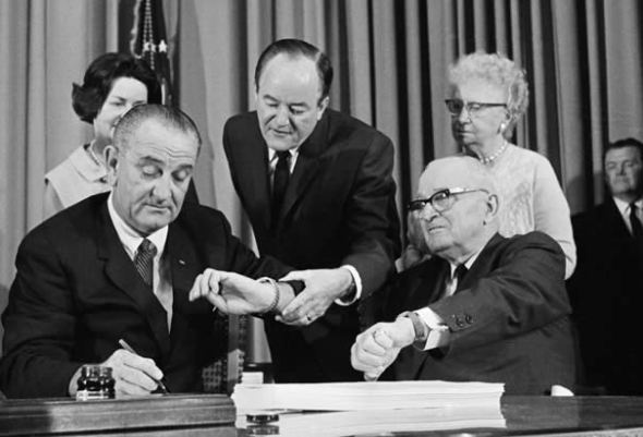 Lyndon B. Johnson signs the Medicare Act of 1964, with Harry Truman by his side