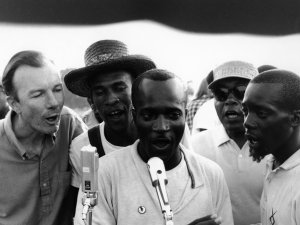 "American folk singer and activist Pete Seeger (left) adopted and helped popularize ""We Shall Overcome"" by teaching the song at rallies and protests. Here he sings with activists in Greenwood, Miss., in 1963. (NPR)"