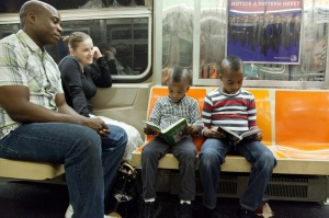 on the left he's reading Diary of a Wimpy Kid The Last Straw, by Jeff Kinney. on the right he's reading Warriors, by Erin Hunter.