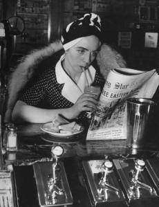 A woman wearing a turban while drinking a chocolate shake and reading the newspaper