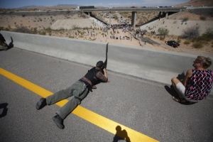 Eric Parker from central Idaho aims his weapon from a bridge as protesters gather by the Bureau of Land Management's base camp