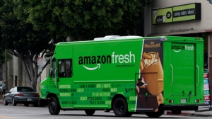 An Amazon Fresh delivery van moves down Pico Bloulevard in Los Angeles