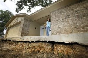 Barbara Brown poses for a photo on the front step of her home that now sits about one foot off the surface of her lawn, Saturday, June 21, 2014, in Reno, Texas.