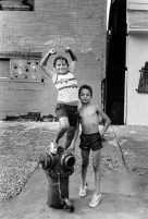 Two boys play on a fire hydrant near E. 91st St., July 18, 1987. Photograph by Antonio Perez