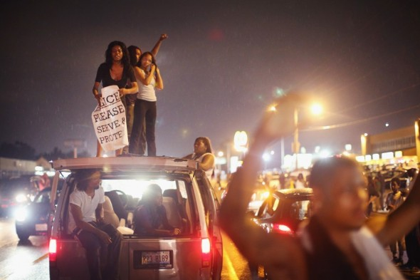 Demonstrators gather along West Florissant Avenue on Friday to protest the shooting of Michael Brown in Ferguson, Mo. Brown was shot and killed by a Ferguson police officer on Aug. 9. Friday's demonstration ended with protesters clashing with police followed by more looting. (Scott Olson/Getty Images)