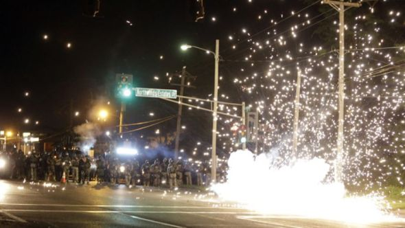August 13, 2014: A device deployed by police goes off in the street as police and protesters clash in Ferguson, Mo. (AP Photo/Jeff Roberson)
