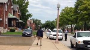 A man identified as Kajiene Powell, with an object in his right hand, approaches police in north St. Louis. Police say that the object was a knife and that he threatened officers before he was shot to death. (St. Louis Police Department)