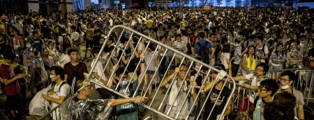 Protestors tie up barricades during a demonstration outside headquarters of the Legislative Counsel on 28 September 2014 in Hong Kong.  Thousands of pro-democracy protesters massed outside Hong Kong's government headquarters vowing to keep up an increasingly tense civil disobedience campaign unless Beijing grants more political freedoms.  AFP PHOTO / XAUME OLLEROS        (Photo credit should read XAUME OLLEROS/AFP/Getty Images)