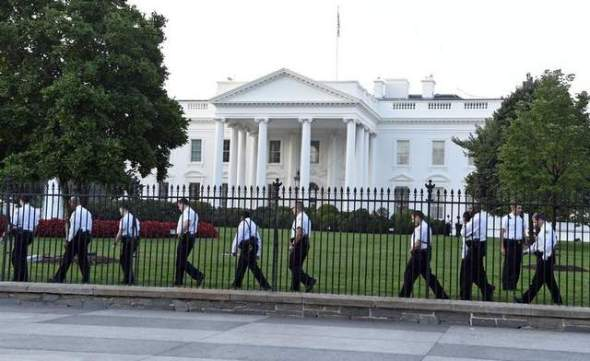 Uniformed Secret Service officers walk along the fence on the north side of the White House on Sept. 20 in Washington. (Susan Walsh / AP)