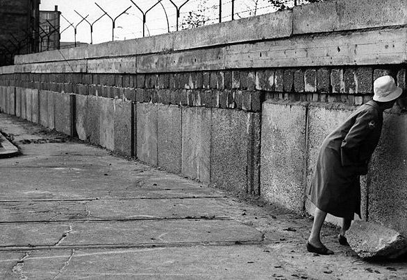 Divided. A woman attempts to peer through the wall in 1961. The erection of the wall split families in half. Many eastern Berliners were cut off from their jobs.