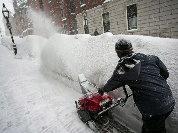 City worker tries to clear a sidewalk in downtown Boston
