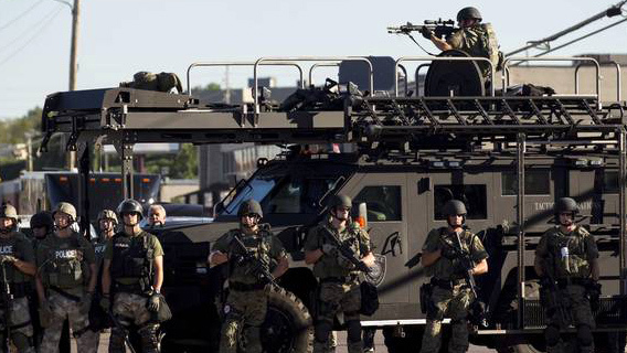 Riot police stand guard as demonstrators protest the shooting death of teenager Michael Brown in Ferguson, Missouri August 13, 2014. Credit: REUTERS/Mario Anzuoni