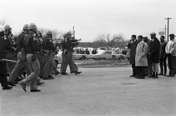 "Two Minute Warning, photo by Spider Martin.  Selma ""marchers facing a line of state troopers in Selma moments before police beat the protestors on March 7, 1965."" The day became known as Bloody Sunday. Courtesy Tracy Martin (NPR)"