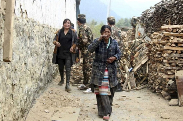 Residents cry as they walk past damaged houses to safer areas, after a 7.9 magnitude earthquake hit Nepal, in Gyirong county of Xigaze Prefecture, Tibet Autonomous Region, China, April 25, 2015. Rescuers dug with their bare hands and bodies piled up in Nepal on Sunday after an earthquake devastated the heavily crowded Kathmandu valley, killing at least 1,900, and triggered a deadly avalanche on Mount Everest. In Tibet, the death toll climbed to 17, according to a tweet from China's state news agency, Xinhua. Picture taken April 25, 2015. REUTERS/Stringer