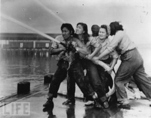 Women firefighters douse flames during the Pearl Harbor attack.