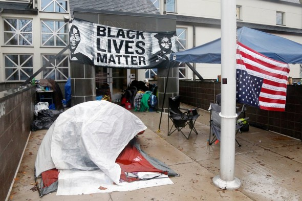 Members of Black Lives Matter continue their encampment, Tuesday, Nov. 17, 2015, outside the Minneapolis Police Department's Fourth Precinct. (AP Photo/Jim Mone)