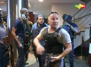 A security officer gives instructions to security forces inside the hotel Photograph: Mali TV ORTM/AP