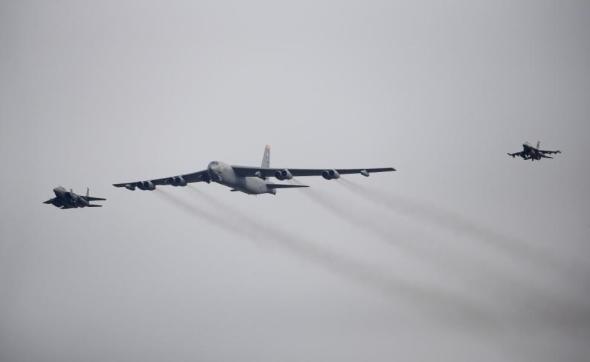 A U.S. Air Force B-52 (C) flies over Osan Air Base in Pyeongtaek, South Korea, January 10, 2016. REUTERS/Kim Hong-Ji