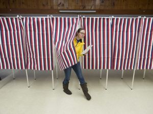 woman exists voting booth, Laonia, NH