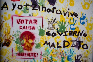"""Graffiti in the central square of Tixtla, home of the rural normal school at Ayotzinapa, reads """"Ayotzinapa lives. Voting causes death. Cursed government,"""" in Tixtla, Mexico, Saturday, June 6, 2015. (AP Photo/Rebecca Blackwell)"""