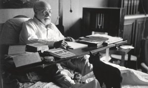 Henri Matisse working in bed, with cat