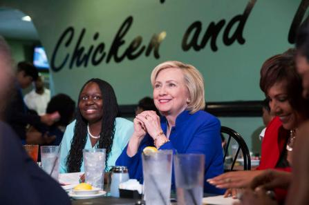 Democratic presidential candidate Hillary Clinton talks with people assembled to meet her while sitting with business leaders Kiki Smith Cyrus (L) and Cynthia Hardy (R) at Kiki's Chicken and Waffles restaurant in Columbia, South Carolina May 27, 2015. REUTERS/Chris Aluka Berry - RTX1ET8O