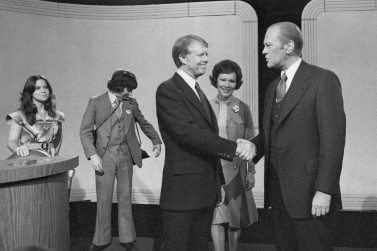 With his wife Rosalynn Carter looking on at center, Democratic presidential candidate Jimmy Carter, center left, shakes hands with President Gerald Ford at the conclusion of their debate at the Palace of Fine Arts Theater, Oct. 6, 1976, San Francisco, Calif. Others unidentified. (AP Photo)