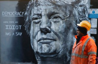 A construction worker stands in front of a piece of street art portraying prospective U.S. Presidential candidate Donald Trump, in east London