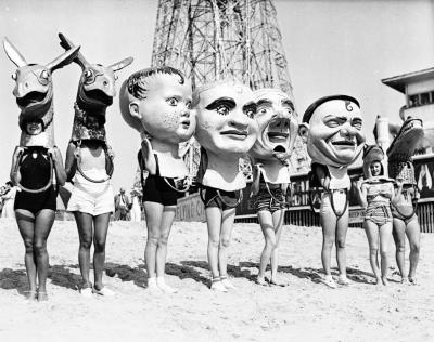 Women wearing oversized masks on the beach in Venice, ca.1930
