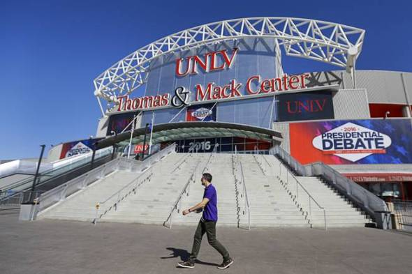 A pedestrian walks past the site for the third presidential debate between Republican Donald Trump and Democrat Hillary Clinton at UNLV's Thomas & Mack Center in Las Vegas, Tuesday, Oct. 18, 2016.