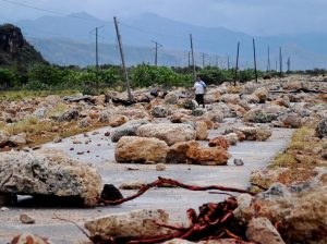TOPSHOT - A woman walks on October 5, 2016 along a coastal road between Guantanamo and Baracoa which was left covered in rocks and severely damaged after the passage of Hurricane Matthew through the eastern tip of Cuba on Tuesday afternoon. Hurricane Matthew, the Caribbean's worst storm in nearly a decade, barreled towards the Bahamas Wednesday morning after killing nine people and pummeling Haiti and Cuba. / AFP / Yamil LAGE        (Photo credit should read YAMIL LAGE/AFP/Getty Images)