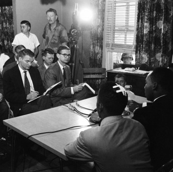 John Lewis, with bandaged head sits next to MLK during press briefing.