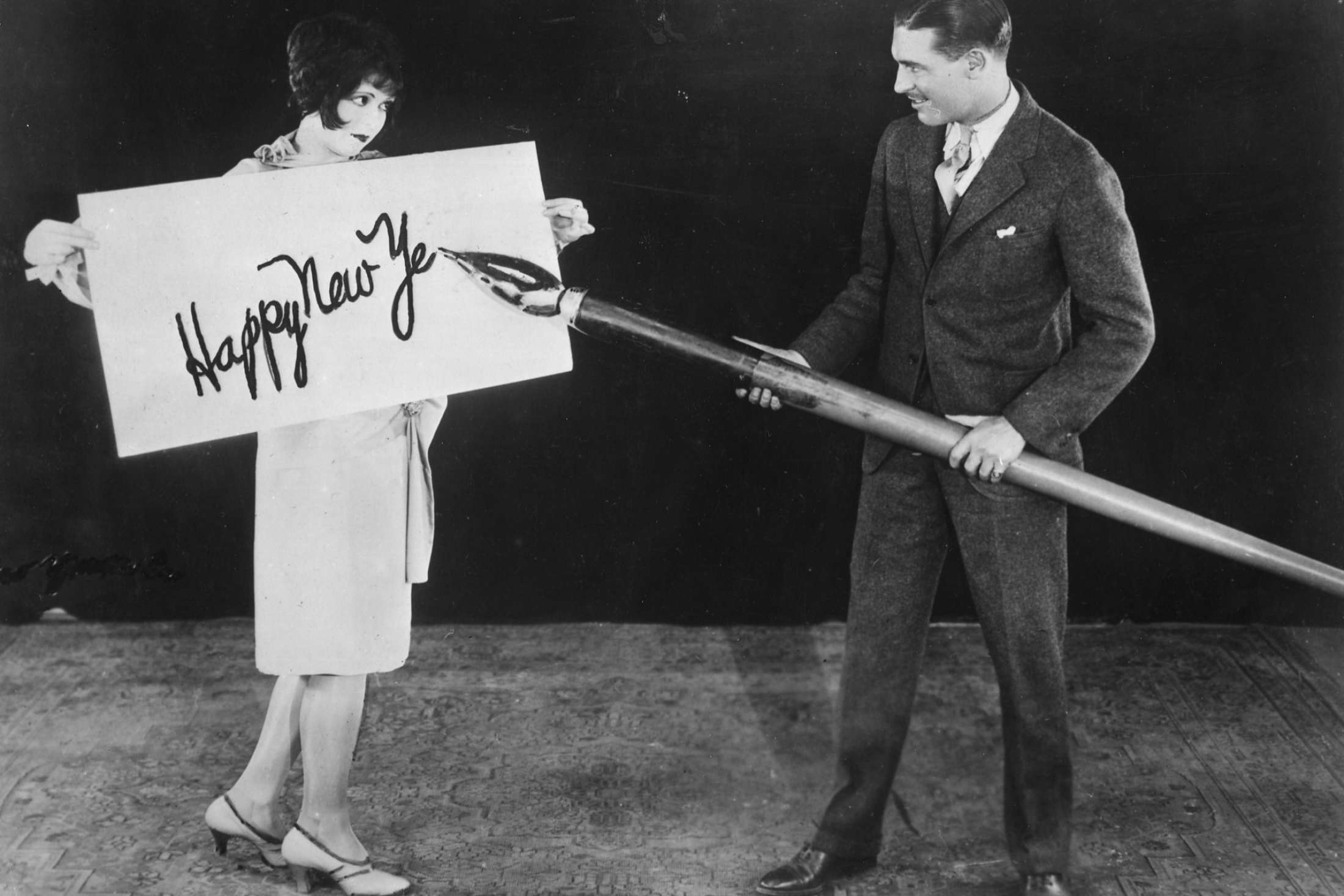 American actress Clara Bow holds up a large card while actor Larry Gray inscribes a New Year's greeting with a giant pen, 1935.