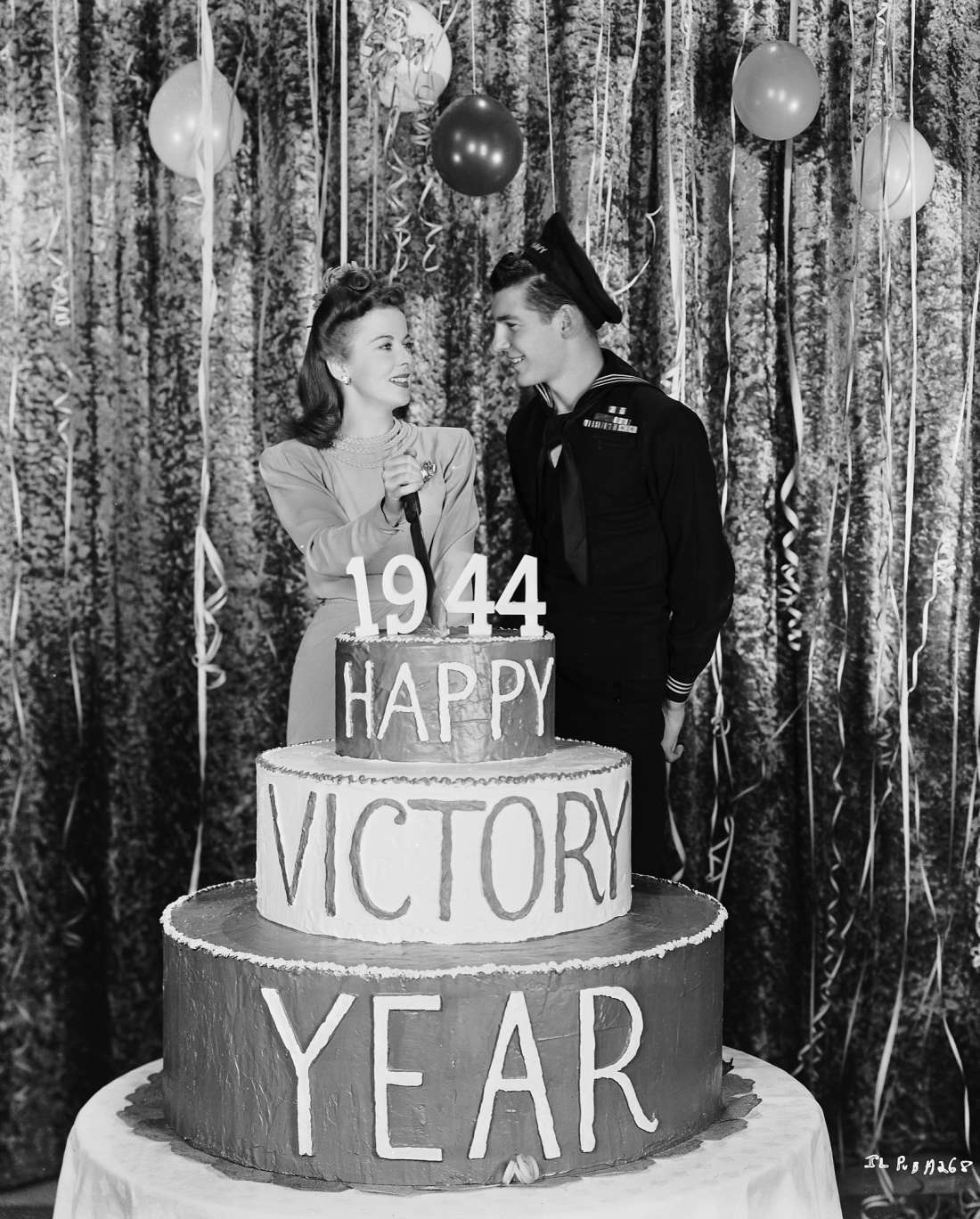 British actress Ida Lupino smiling at a friendly sailor as she cuts a cake which reads Happy Victory Year, 1944.