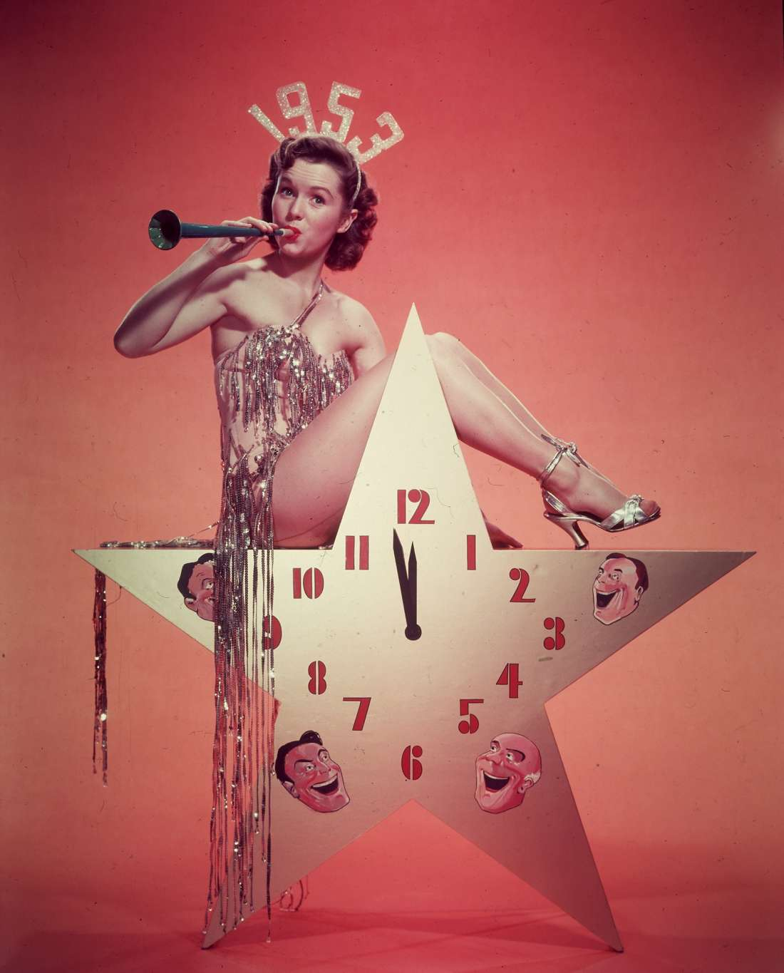 Debbie Reynolds, wearing a 1953 tiara and a costume with tinsel, blows a horn while sitting atop a star-shaped clock in a promotional portrait for New Year's Eve.