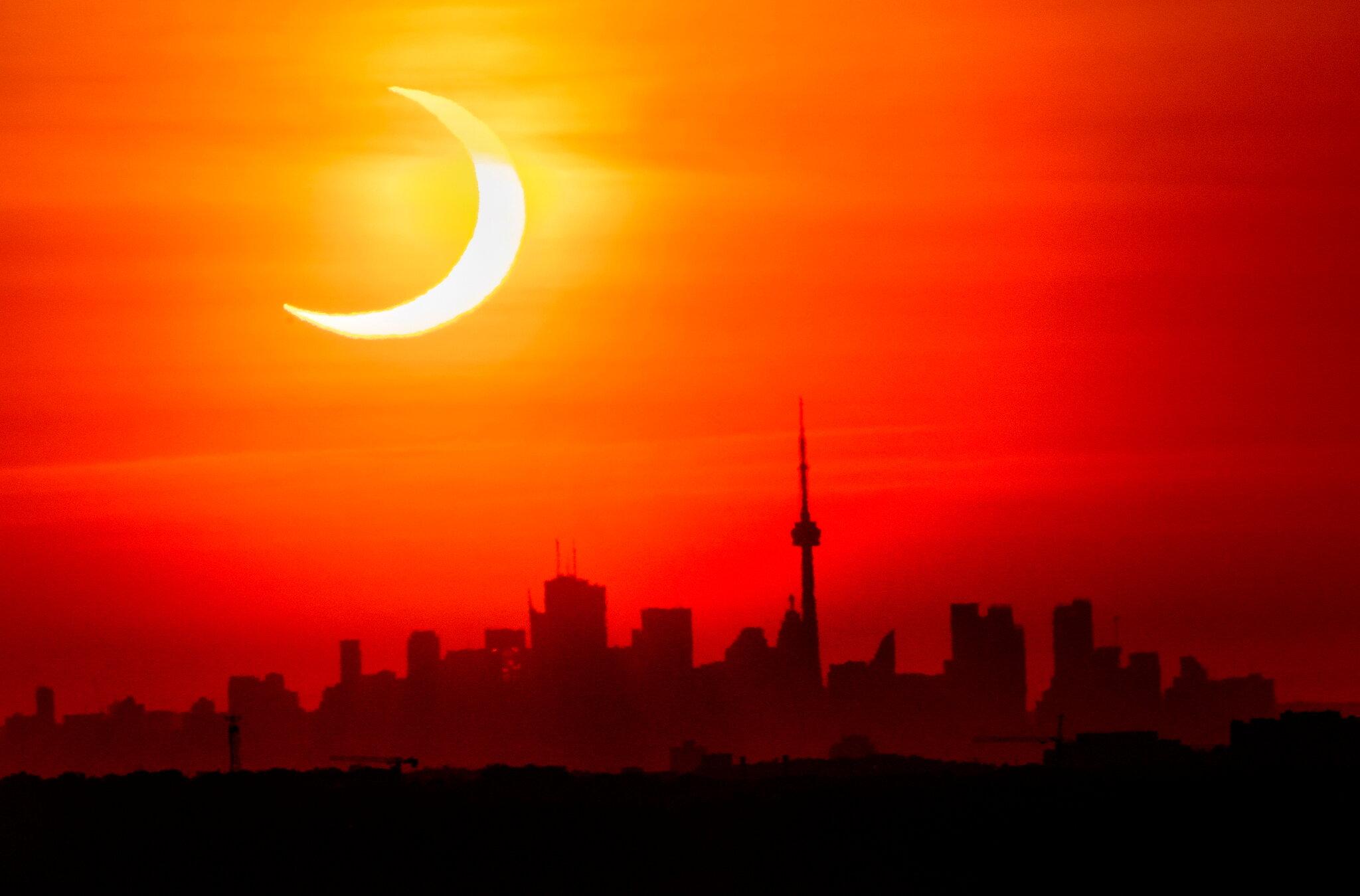 Thursday's eclipse over the Toronto skyline.Credit Frank Gunn, The Canadian Press, via Associated Press