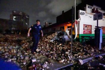 New Orleans Police detective Alexander Reiter, looks over debris from a building that collapsed during Hurricane Ida in New Orleans, Monday, Aug. 30, 2021.